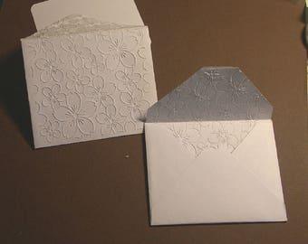 8 petites enveloppes  blanches   gaufrées,  motif floral
