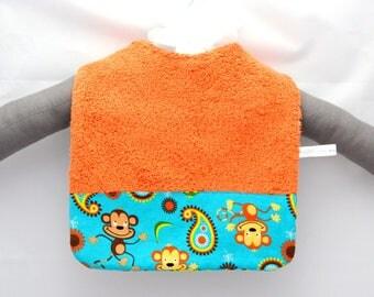 Orange baby bib with monkeys