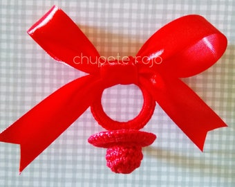 Red ribbon with crochet pacifier to decorate