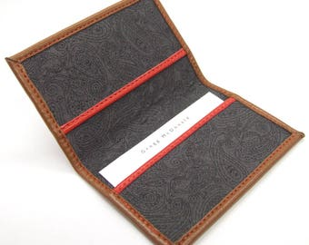 Tan leather card holder, paisley lining, red details