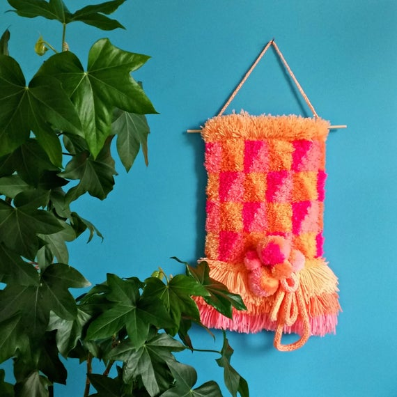 Pastel yarn woven wall hanging with pom pom details.