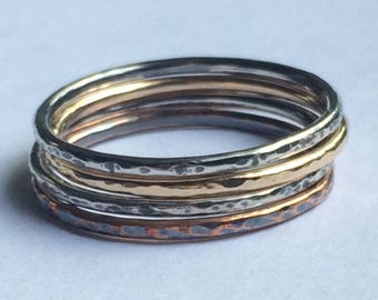 Mixed metal stack ring set with solid 14 k yellow gold , sterling silver , and copper hammered thin bands with oxidized patina