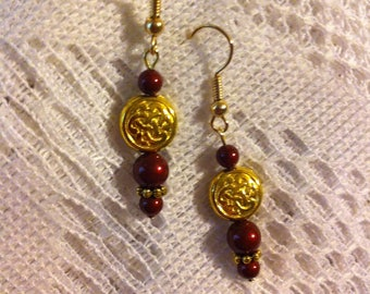 Bordeaux and Gold plated pierced earrings with Celtic knot beads.