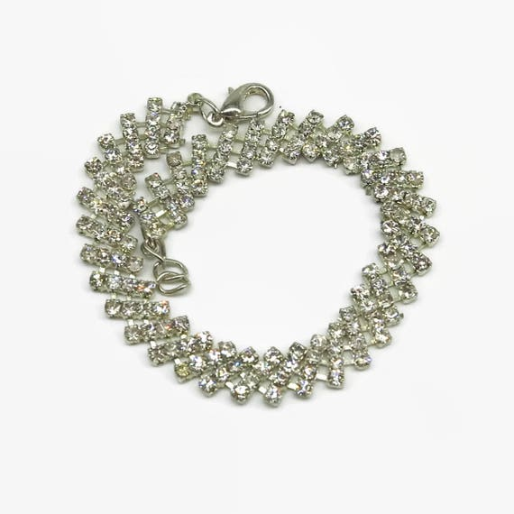 Rhinestone bracelet in silver plated metal setting, diagonal bars with 3 rhinestones that are connected in a concertina fashion for movement