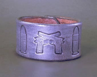 """Guns and Bullets! Leather cuff stamped with crossed pistols and bullets - Metallic silver - Size 7"""""""