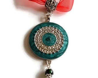 Green and silver round pendant with a red glass droplet on a red ribbon necklace