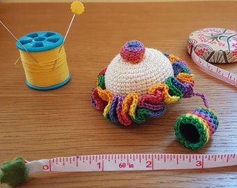 Exquisite crocheted pincushion with attached thimble in rainbow cover.