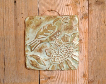 Goldfinch singing on sunflower, square tile with copper green patina glaze.