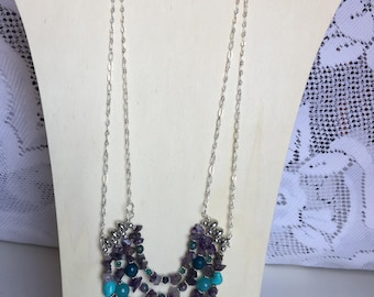 Necklace with 4 strands of amethyst agate and crystal.