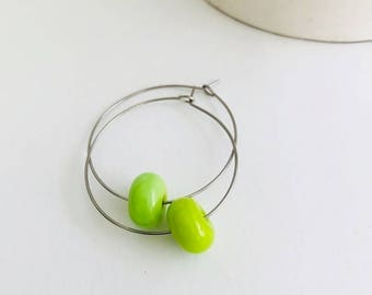 Earrings loops with green pea glass beads .