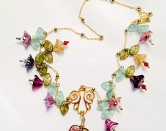 Glass flower blossom necklace in rainbow colors on delicate gold-plated chain with heart pendant