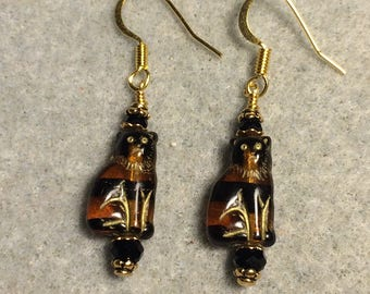 Small brown and black Czech glass cat bead dangle earrings adorned with black Chinese crystal beads.