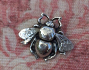 A beautiful silver coloured brooch in the shape of a bee.