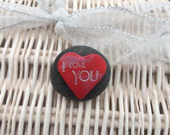 "Red clay heart inscribed ""I love You"" mounted on a black pebble"