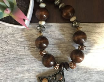 Necklace with metal pendant and wooden beads with matching earrings