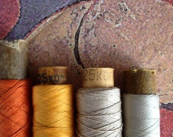 Spools of cotton threads in set. 4 spools in set: orange, yellow, natural colors.