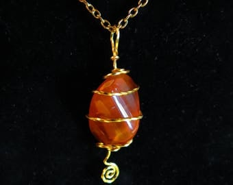 203 Caged wrapped Carnelian agate in gold