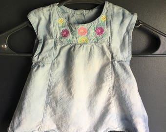 9 month short sleeve shirt with flower design on front, bleach dyed to make the soft denim turn into different blues