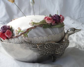 adorable quilted pillow needle silk mounted on a silver tray with its Garland