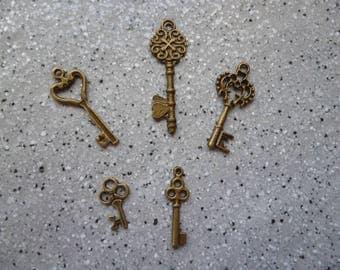Lot de 5 breloques clés en métal bronze.