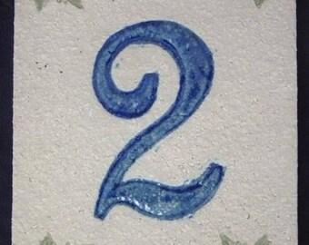Door number, number '2' deep blue, leaves of Ivy on a beige background