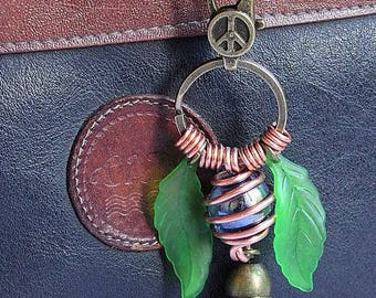 """Bag charm with turquoise glass bead wrappee and adorned with leaves and a tassel: """"Light"""" - black"""