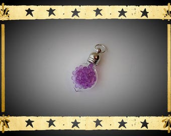 A glass Teardrop vial flattened filled with micro purple bead