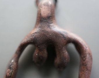 Neolithic goddess clitoris pendant in bronze, weathered fire / clit-goddess pendant with patina