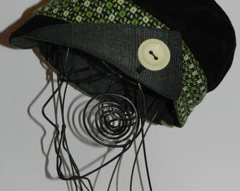 "Black and green cap newsboy style with asymmetrical visor ""buttoning""."