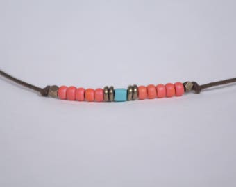 Blue and coral glass beads on a waxed-cotton cord. Wear 4 ways.