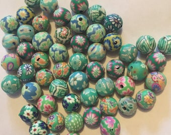 Pack of 54 x 10mm polymer clay round mix of green themed flower etc beads.