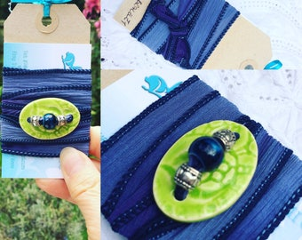 Silk wrap bracelet with lime green cental oval hand made button with silver tone and blue bead