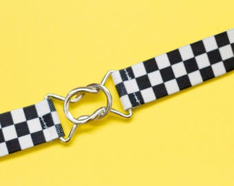 Skinny black and white checkerboard elastic waist belt with interlocking clasp