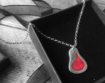 Solid silver pendant with shades of pink/red/orange enamel.