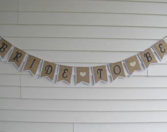 "Rustic Burlap ""BRIDE TO BE"" Banner - Bridal Shower Party Decor Shown in White with Navy Blue Lettering"