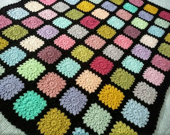 Hand made crocheted blanket featuring bright coloured starburst flowers on a black background 134x118 cm / 53x43 inches