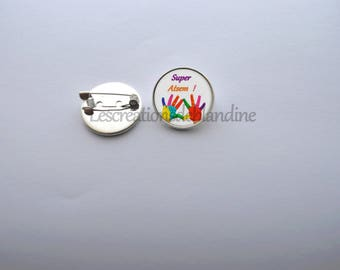 """Brooch """"special school"""", it measures 20mm in diameter and is covered with a glass cabochon"""