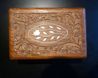 """This is a hand carved, floral pattern wooden trinket box with a white bone inlay. It is 6"""" wide, 4"""" deep and 2.5"""" tall."""