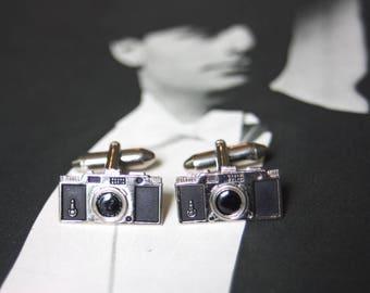 A pair of vintage 35mm camera cufflinks.