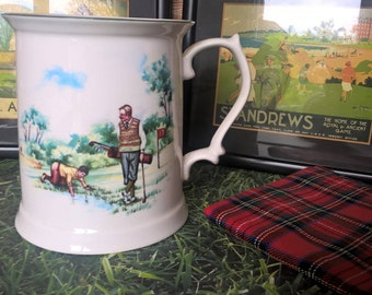 Golf mug / tankard with golfer in plus fours and caddy searching for ball in water. On the back clubhouse and motto Still Waters Run Deep