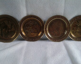 4 Vintage Brass ashtrays with etched camels and house in the center.
