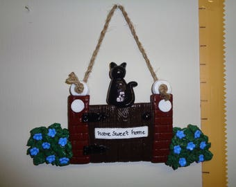Decorative salt dough wall hanging of cat sitting on garden gate with flowery shrubs 15cm tall. 26cm tall hanging rope
