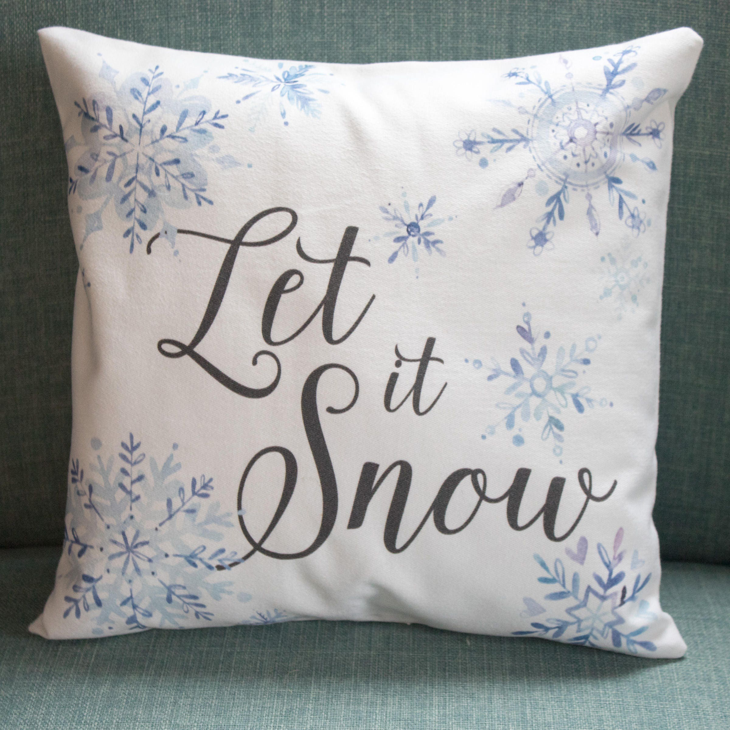 Let it Snow winter decor throw pillow with blue watercolor snowflakes