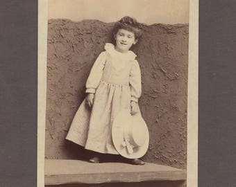 Amusing Cabinet Card of a Smiley Little Girl Against a Rough Backdrop