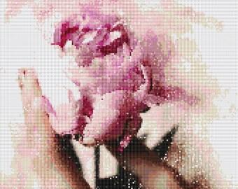 Holding a Pink Rose Cross Stitch Pattern