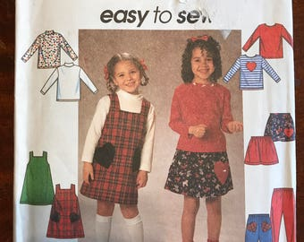 Simplicity 7742 - Easy to Sew Girl's Jumper, Top, Skirt, and Pull On Pants with Heart Pocket and Applique Options - Size 2 3 4 OR 5 6 6X