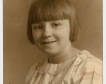 1920s vintage portrait photograph, huge hair bow, young girl, short bob, straight fringe, cotton dress, old sepia photo postcard, Kathleen