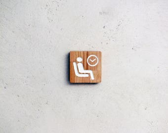 Wooden door sign with engraved waiting room pictogram. Wood signage for doctor office.