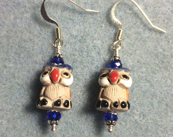 Small tan, red, and dark blue ceramic owl bead earrings adorned with dark blue Chinese crystal beads.