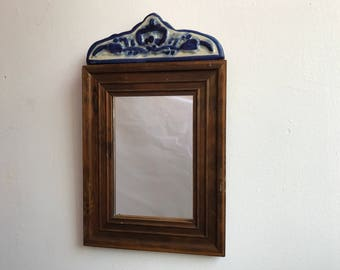 Vintage mirror, framed in wood with talavera detail on top.
